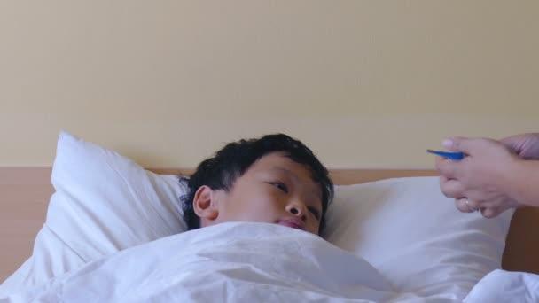 kranker Junge liegt im Bett und Mutter überprüft seine Temperatur
