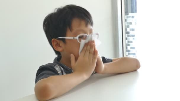 chlapec maže jeho sopel papírem