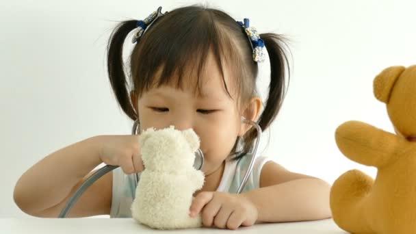 dívka si hraje s hračkou stetoskop a medvěd