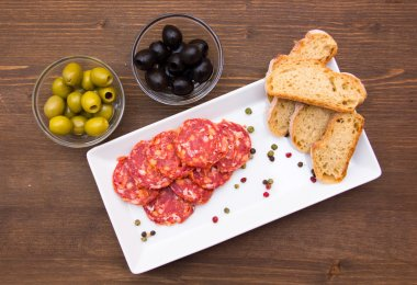Antipasto of salami and olives on wood from above