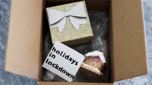 winter holidays in lockdown, gifts being delivered via postal parcel with Christmas themed items inside of it and hand removing memo about lockdown