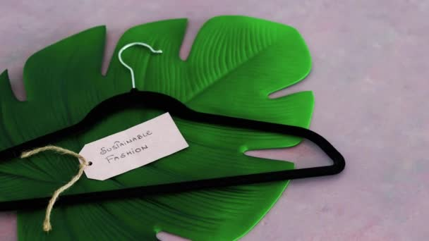 Sustainable Fashion label with clothes hanger on top of tropical green leaf on pink background shot at shallow depth of field, concept of environmentally conscious clothing brands