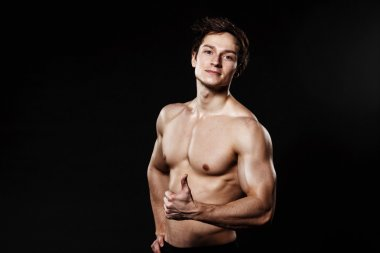 Muscular and fit young bodybuilder fitness male model showing th