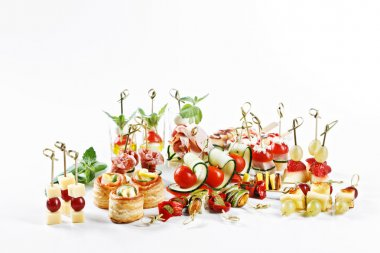 Great attractive set of canapes with vegetables, cheese, fruits, berries, salami, seafood, meat and decoration on white background studio isolated with space for text template