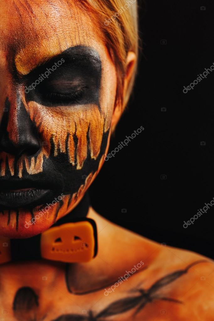 halloween portrait of body art pumpkin close eyes girl with pumpkin bowtie on black background. Real greasepaint and face art makeup. half face. modern costume