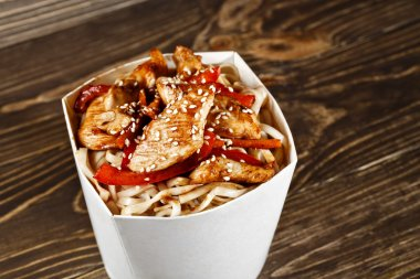Delicious wok noodles box container with udon and chicken on woo