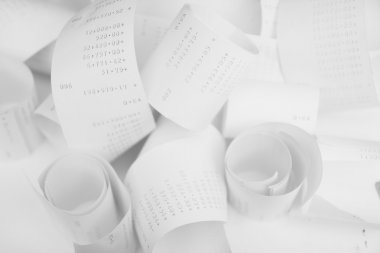 Paper cash register receipts in a lose pile close up with soft f