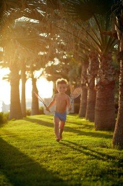 Cute little boy in swimming trunks walking along palm alley