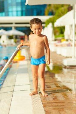 Cute little boy posing near outdoor swimming pool