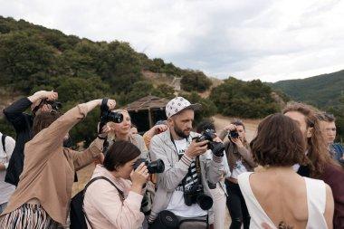 Bir grup fotoğrafçı dağlarda düğün çifti çekiyorlar.