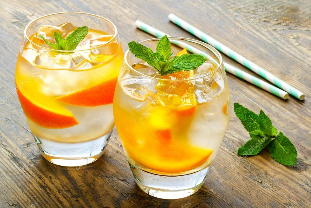 Cold drinks with ice and mint. Orange cocktail on rustic wooden table