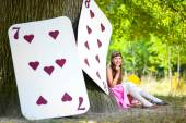 Photo Girl near the large cards under huge oak tree. Alice in Wonderland concept