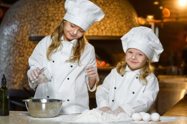 Making the dough for pizza is fun - little chefs playing with flour