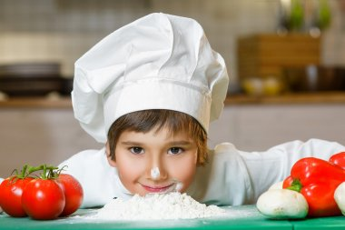Funny happy chef boy cooking at restaurant kitchen and bent over the flour