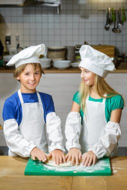 Funny happy chef boy width girl cooking at restaurant kitchen and rolls the dough with a rolling pin