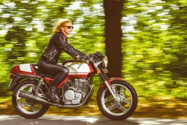 Active girl riding on the motorbike, slow motion, having fun in bikers tour, vintage style photo, happy adventure concept