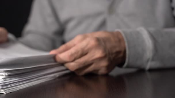 Close-up of a mans hands, reads and leafs through documents.