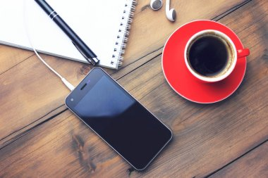 coffee, phone, earphone, notebook and pen on table