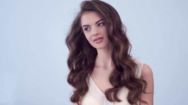 Schöne Frau mit langen lockigen braunen Haaren. Modemodel blickt im Studio in die Kamera. Nahaufnahme Gesicht einer attraktiven brünetten Frau. Sexy Model mit einem saexy Look. 4k Filmmaterial. Zeitlupe.