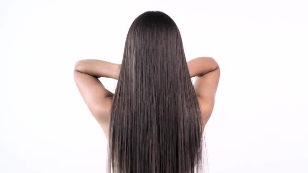 Žena hýbe dlouhými vlasy. Zadní pohled. Dívka třese dlouhými rovnými vlasy. Ženský model se třese. Zpomalené záběry. Zadní pohled.
