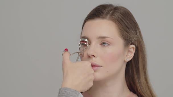 Visagiste Curling Wimpern mit Wimpernzange. Make-up-Artist im Studio Make-up für schöne Mädchen. Junge Frau beim Make-up im Fotostudio. Mua machen.