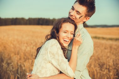 Young couple in love outdoor. Stunning sensual outdoor portrait of young stylish fashion couple posing in summer in field. Happy Smiling Couple in love. They are smiling and looking at each other