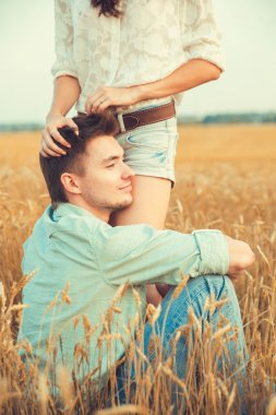 Young couple in love outdoor. Stunning sensual outdoor portrait of young stylish fashion couple posing in summer in field. Happy Smiling Couple in love. They are smiling and looking at each other. Valentine day stock vector