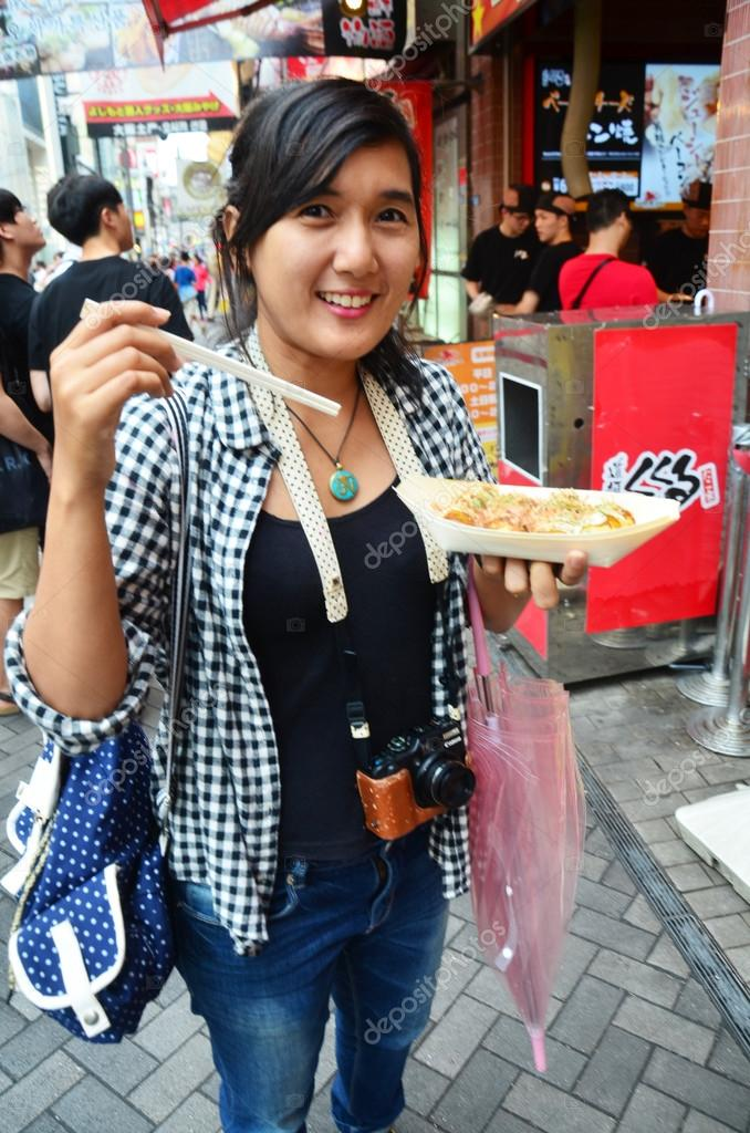 Thai woman eating takoyaki