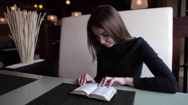 lány egy kávézó, egy könyvet olvas