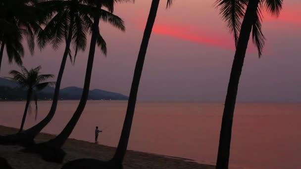 Rybář při západu slunce na pláži