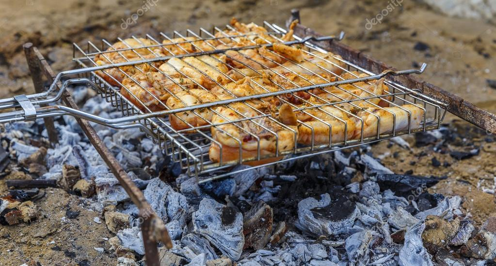 Cooking chicken on skewers on the beach(soft focus)
