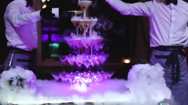 Sklenice s alkoholickými nápoji v pyramidě, plnění a nalévání krásné pyramidy řadu různých barevných alkoholických koktejlů se šampaňským na párty, catering banket