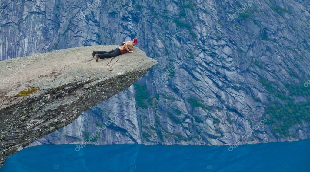 A vibrant picture of famous norwegian hiking place - trolltunga, the trolls tongue, rock skjegedall, with a tourist, and lake ringedalsvatnet and mountain panoramic scenery epic view, Norway