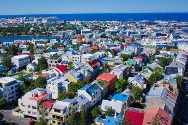 """Картина, постер, плакат, фотообои """"красивый супер вид с воздуха широкого угла Рейкьявика, Исландия с гаванью и горами горизонта и пейзажем вне города, замеченного по башне наблюдения hallgrimskirkja собора."""", артикул 61779061"""