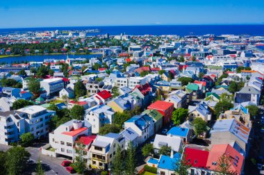 Beautiful super wide-angle aerial view of Reykjavik, Iceland with harbor and skyline mountains and scenery beyond the city, seen from the observation tower of Hallgrimskirkja Cathedral.