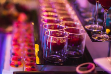 Beautiful line of different colored cocktails with smoke on a Christmas party, tequila, martini, vodka, and others on decorated catering bouquet table on open air party