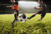 Photo Two soccer players kicking a soccer ball