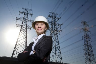 Businesswoman in front of power lines