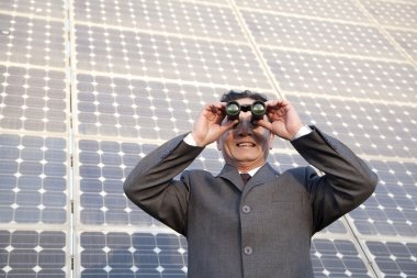 Businessman looking through binoculars in front of solar panels
