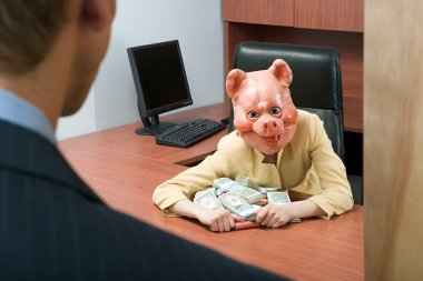 Businesswoman in pig mask holding money