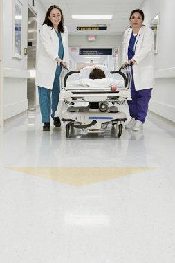 Doctors pushing patient in bed through corridor