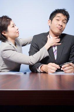 Businesswoman strangling businessman