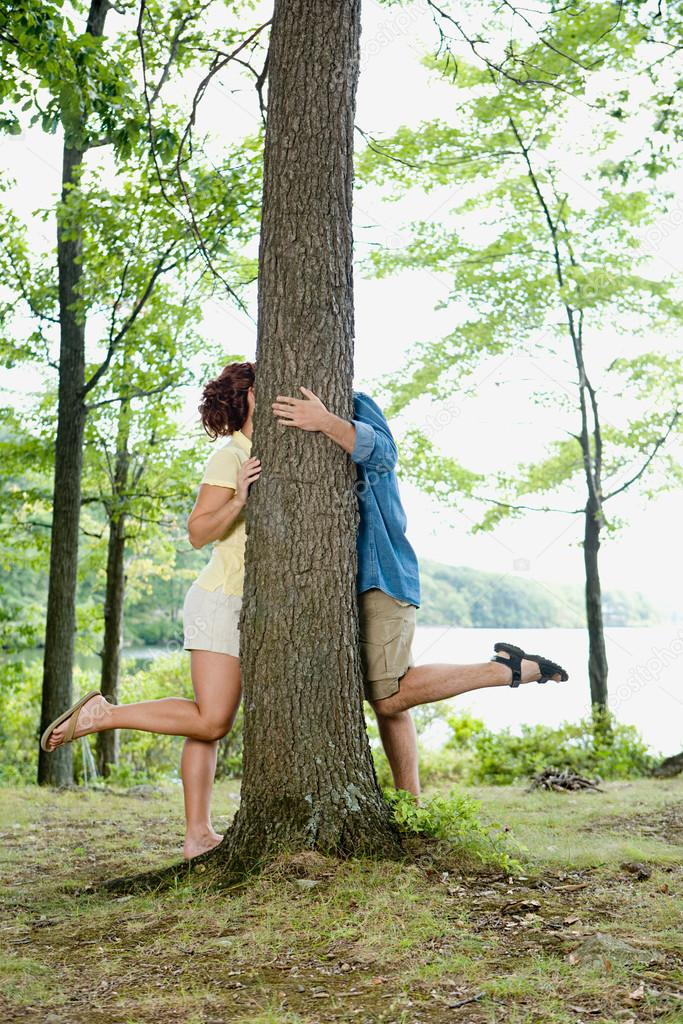 Couple kissing behind a tree