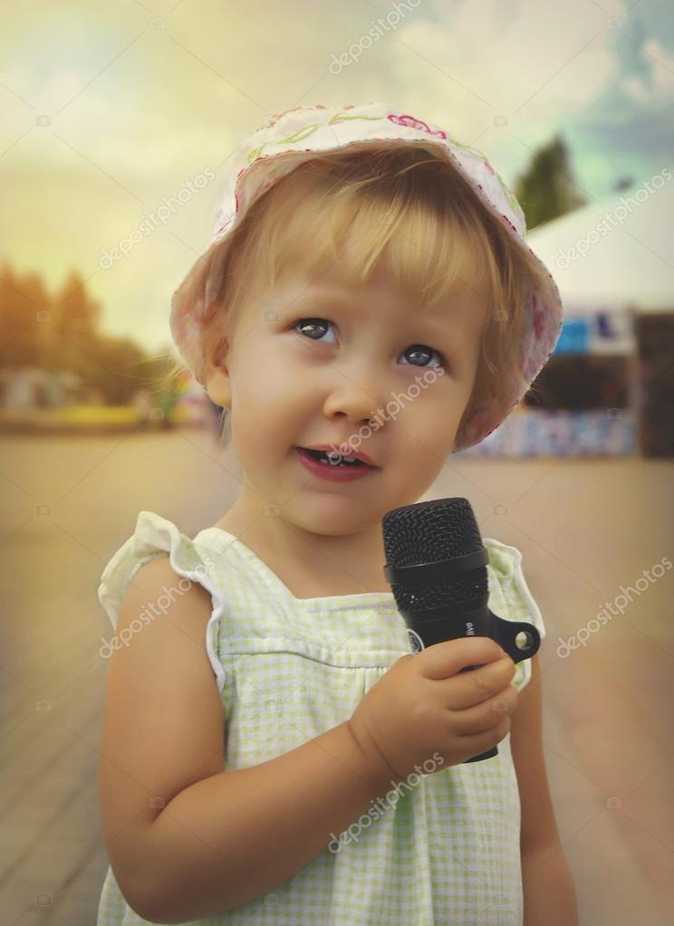little girl is singing holding  a microphone