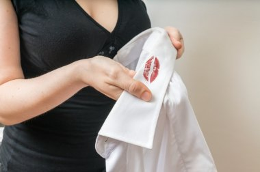 Cheating and infidelity concept. Woman holds white shirt of her husband with red lipstick stains on collar.