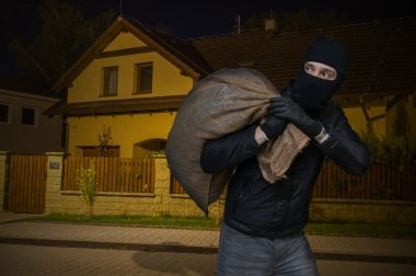 Masked robber or burglar robbed house at night and runs away wit