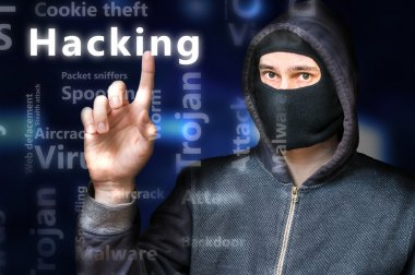 Masked anonymous hacker is pointing on Hacking tag