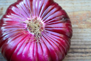 Big red onion on wooden table