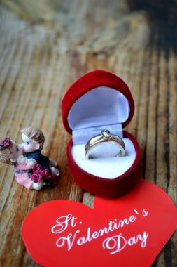 Red heart shaped ring box with platinum engagement ring, angels and a Valentine's card  on wooden table