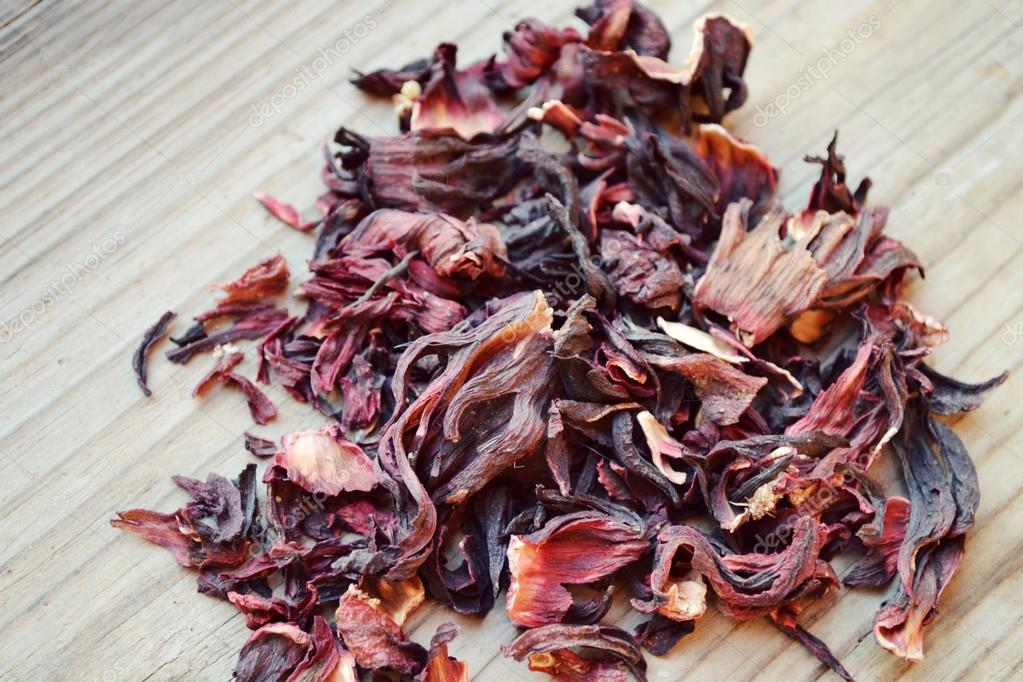 Dry Leaves And Petals Of Hibiscus Tea On Wooden Table Stock Photo